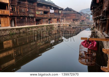 Zhaoxing Dong Village Guizhou Province China - April 9 2010: Wooden houses of farmers reflected in the water of the rural river cage with a bird hanging outdoors.
