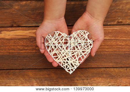 heart in the children's hands on the wooden background