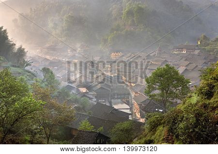 Wooden house dong ethnic minority village in a mountainous southwestern China misty dawn spring time, Zhaoxing Dong Village Guizhou Province China.