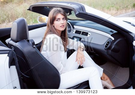 business Lady sits in white cabriolet, travel