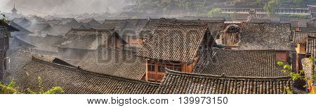 Liping County Qiandongnan Miao and Dong Autonomous Prefecture Tile roofs of wooden houses in a large ancient village panoramic picture, Zhaoxing Village Guizhou Province China.