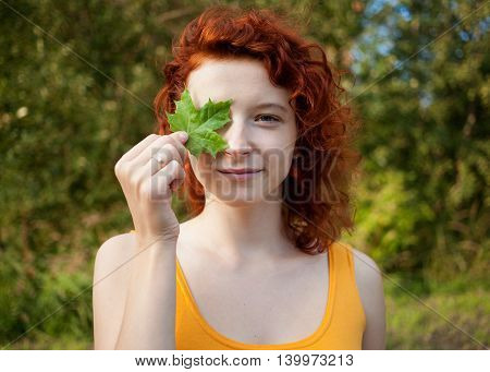 Close up portrait of a ginger girl carrying a maple leaf at the eye