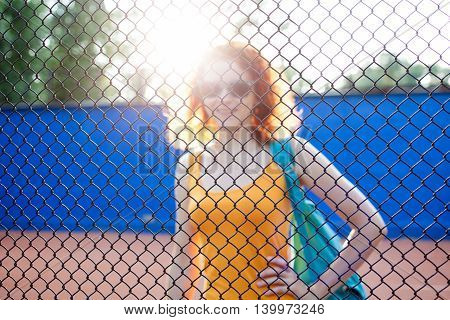 Young ginger woman in sunglasses with a bag on a sports ground view through the grid model are out of focus