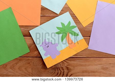 Paper card with happy hippo and a palm tree, colored paper sheets on a wooden table. Kindergarten art and craft activity for kids. Fun children background