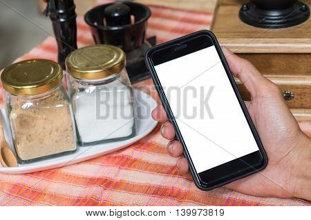 Close up of a man using smart phone with blank mobile and cup of coffee .Smart phone with blank screen and can be add your texts or others on smart phone.