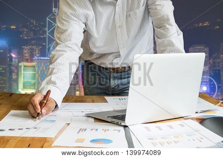 close up of business man hand holding pen for working on laptop computer with business graph information diagram on wooden desk with hong kong night cityscape background. vintage effect.