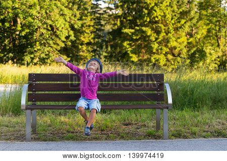 Adorable little boy with arms spread in the air sitting on a bench expressing happiness excitement joy for life and freedom.True emotions.