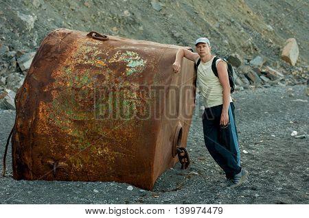man standing on the beach near a huge rusty buoy