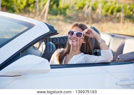 girl in glasses sitting behind the wheel of a white convertible
