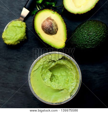 Halved avocados. Top view spread. pasta. Traditional Mexican sauce Guacamole on dark background.