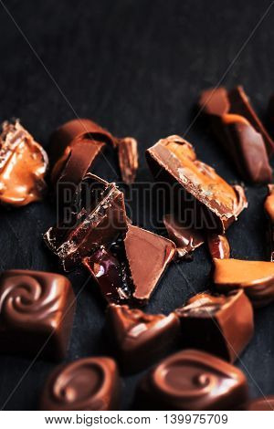 Luxury Chocolate over black background. Chocolate Candy Cocoa. Assortment of fine chocolates close up