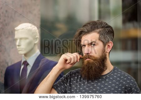 handsome bearded young man hipster with long beard and mustache has stylish hair on serious hairy face standing near shop glass showcase with dummy in suit closeup
