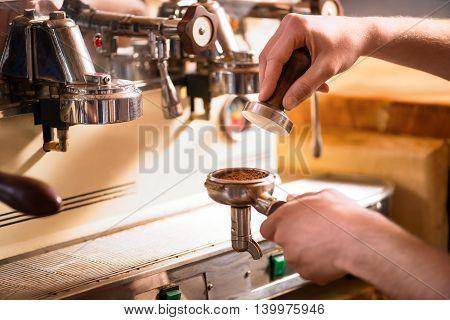 Preparing coffee. Cropped image of male barista preparing fresh coffee