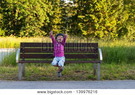 Adorable little boy sitting on a bench making faces expressing happiness and excitement. True emotions.
