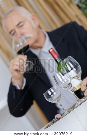 senior man tasting wine thinking deeply on life