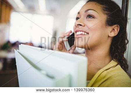 Close-up of businesswoman holding files while using mobile phone in office cafeteria