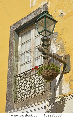 Window and lamp on house in side street of Funchal Madeira Portugal. With peeling paintwork