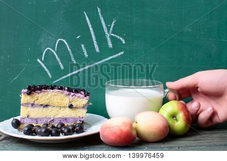 glass cup of fresh natural healthy milk and text word on green school blackboard with blueberry cake on plate and green red apples with human hand copy space