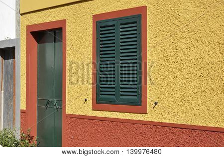 Green door and shuttered window in yellow and orange wall. Funchal Madeira Portugal