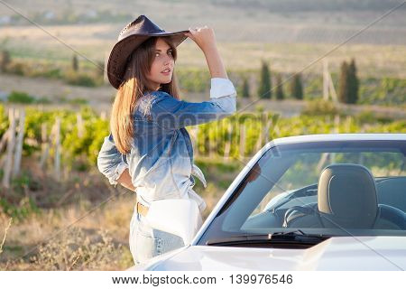 beautiful woman cowboy stands at White convertible