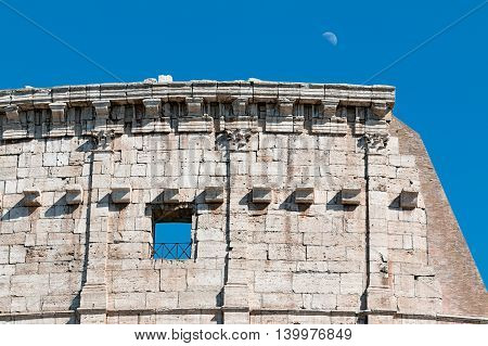 detail of colosseum with moon in blue sky