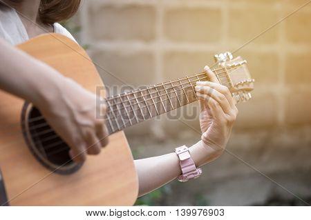 Relaxing time woman playing guitar in garden.
