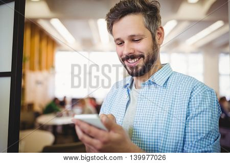 Happy businessman using mobile phone in office cafeteria