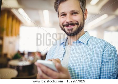 Portrait of happy businessman using mobile phone in office cafeteria