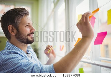 Happy businessman sticking adhesive notes on window at creative office