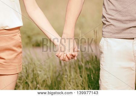 Couple holding hands, close up