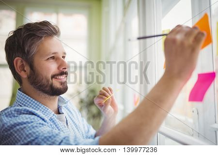 Smiling businessman writing on adhesive notes at creative office