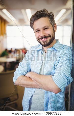 Portrait of cheerful businessman with arms crossed in office cafeteria