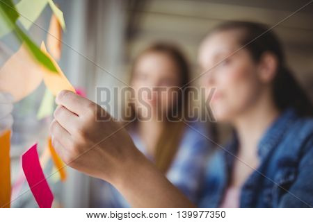 Businesswoman with colleague holding adhesive notes on window in creative office