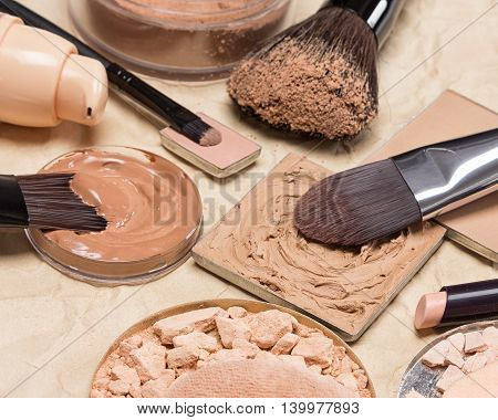 Stick concealer, correcting cosmetic powders, cream-to-powder and liquid foundation on crumpled aged paper. Makeup products to even out skin tone and complexion. Shallow depth of field