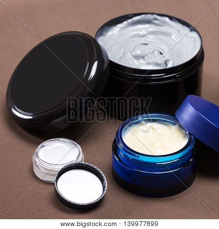 Several open jars of different sizes filled with creams on brown background, focus on blue jar. Various skin care cosmetic products. Skincare for men