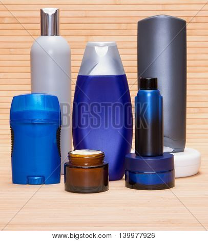 Men's cosmetics. Face and body moisturizing creams, aftershave lotion, antiperspirant deodorant and other cosmetic products for men on wooden surface