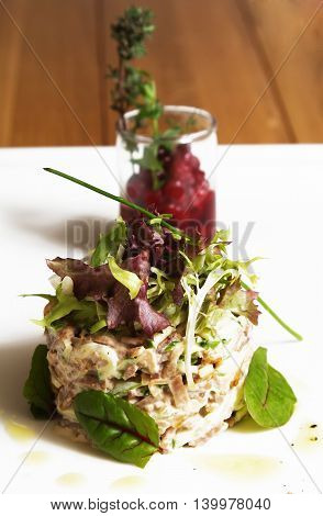 Fish tartare with cranberry sauce and salad