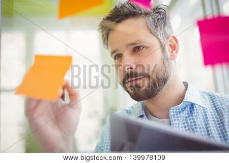 Young businessman writing on adhesive notes at creative office
