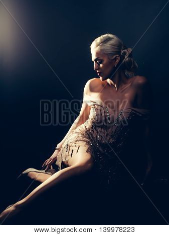 Pretty woman with blonde hair splendid body and legs dressed in glamour beige sexy dress with sequins posing on dark background studio