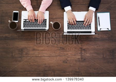 Man and woman working on laptops
