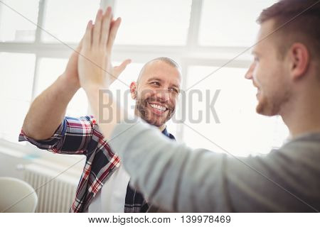 Male coworkers giving high-five in creative office