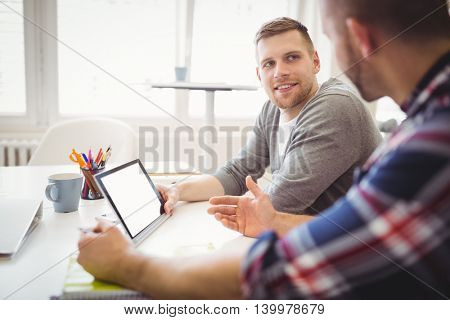 Young businessmen discussing while using digital tablets in creative office