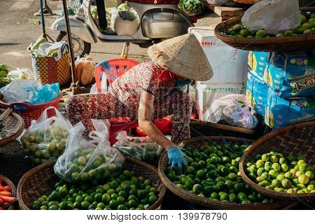 NHA TRANG VIETNAM - JULY 14: Vietnamese woman in conical hat sells fruits and vegs at the morning market in Nha Trang Vietnam on July 14 2016.