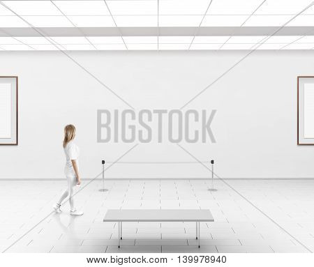 Modern gallery wall mockup. Woman walk in museum hall with blank wal with frames. White clear stand mock up show. Display artwork presentation. Art design empty floor. Expo studio wall in center.