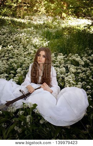Beautiful Young Woman In A Forest Holding A Long Sword