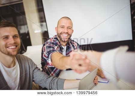 Smiling business people shaking hands in creative office