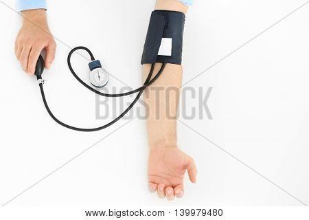 Male hands with tonometer on white background