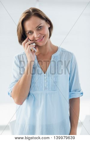 Portrait of young woman talking on mobile phone at home