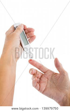 Cropped image of woman using blood glucose monitor against white background