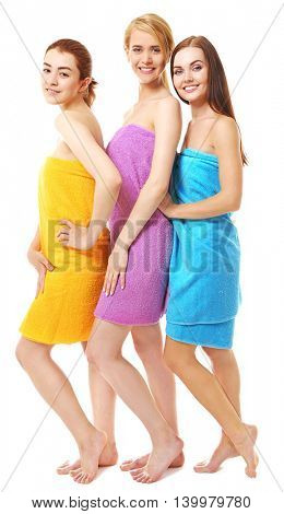 Three beautiful women wrapped in towels isolated on white